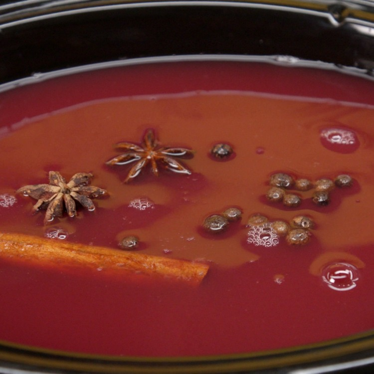 Add star anise pods to spiced cranberry apple cider in slow cooker