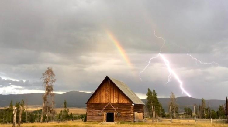 rainbow and lightning bolt behind cabin