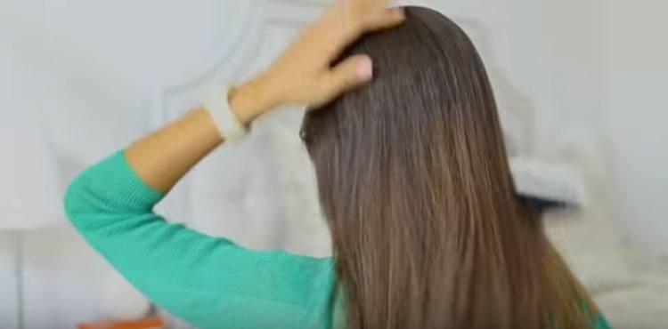 Brush hair back to prepare for ponytail trick