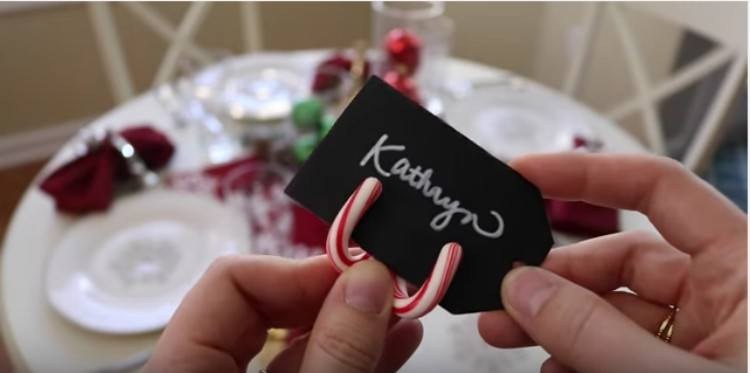 woman placing namecard into candy cane holder