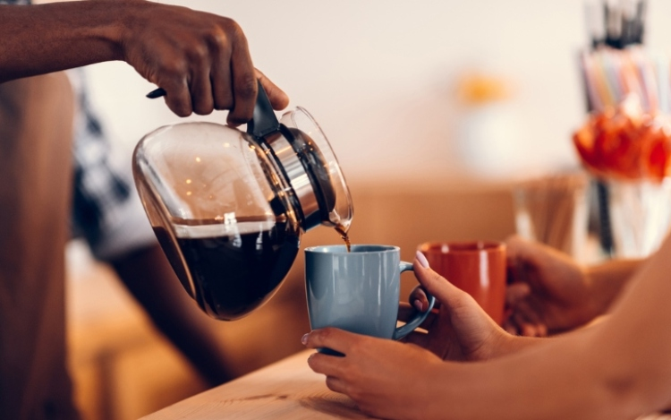Black coffee being poured into mug.