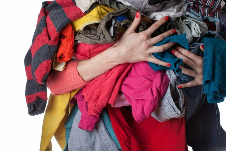 woman holding big bundle of clothing