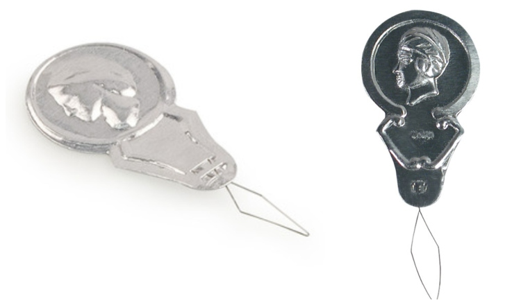 Image of needle threaders with coins on top
