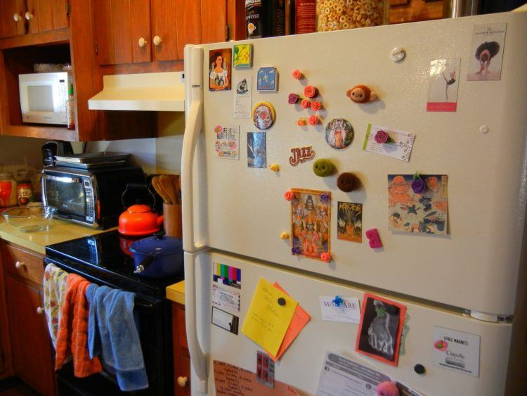 Fridge cluttered with magnets.