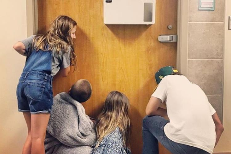 Gaines kids listening at a hospital room door.