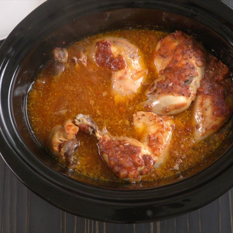 Zesty BBQ chicken cooking in slow cooker