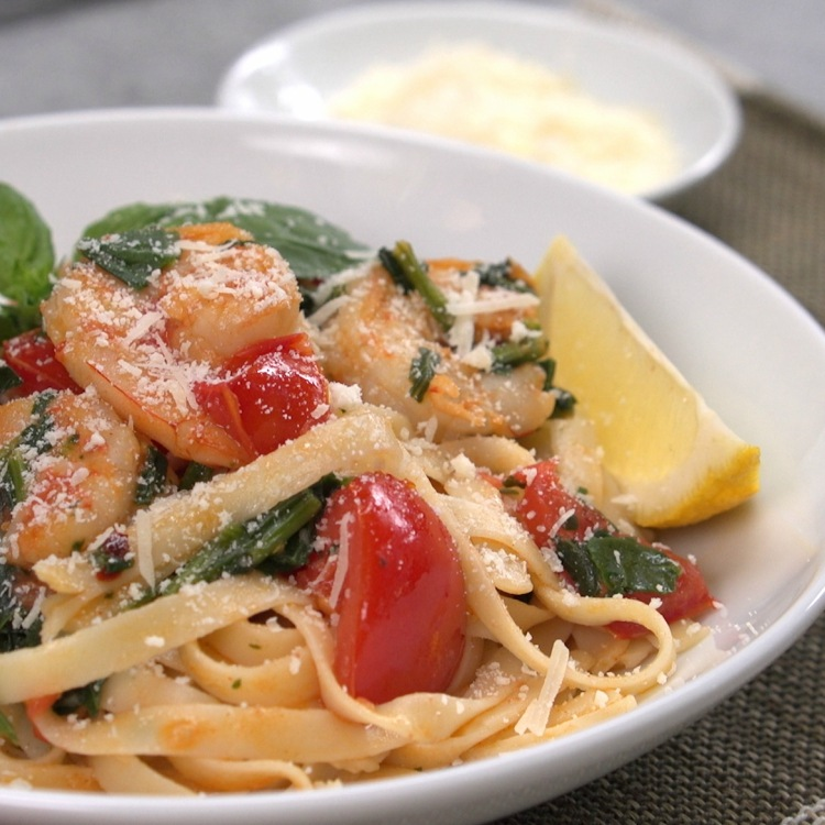 Shrimp tomato and spinach pasta on white plate