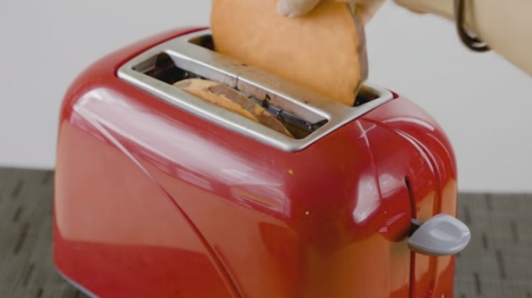 Sweet potato slices going into a toaster.