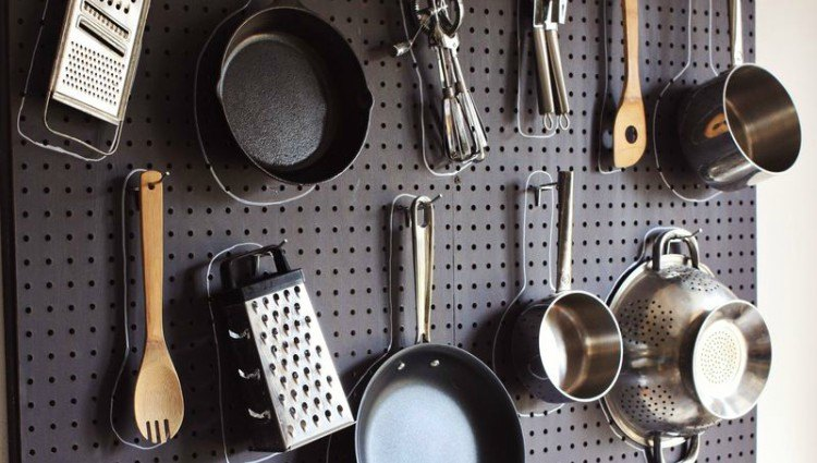cookware hanging from a black peg board