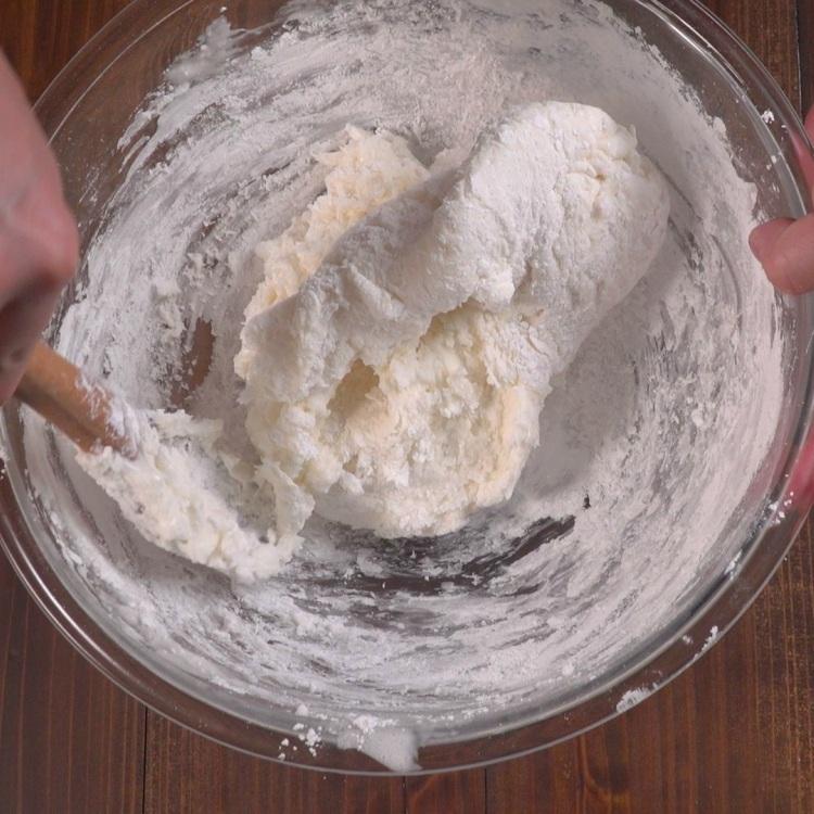 Stirring powdered sugar into melted marshmallows to make fondant
