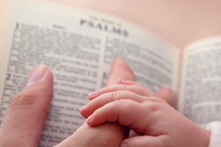 Image of baby holding father's finger as he points to Psalms verse