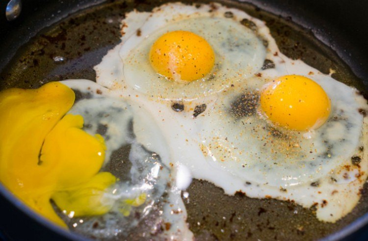 view of broken egg yolk with fried eggs