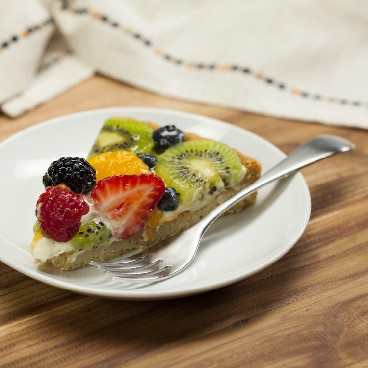 sugar cookie fruit tart slice on plate with fork