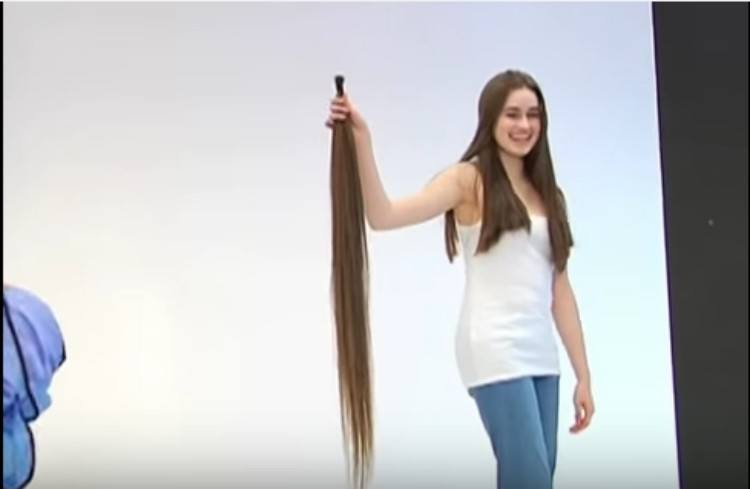 Roxy holding up donation hair