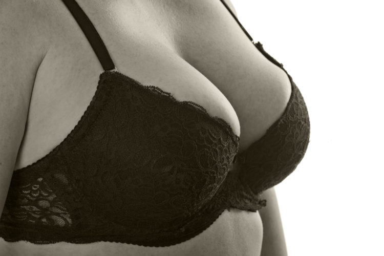 Image of Big breasts middle-aged woman in black bra (sepia), close-up