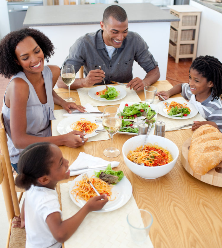 Image of smiling family dining together in the kitchen