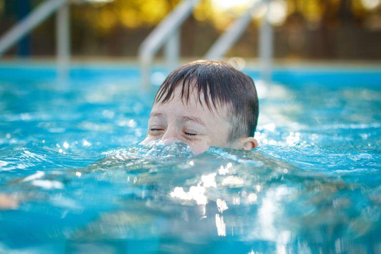 Little preschooler boy playing submarine pool