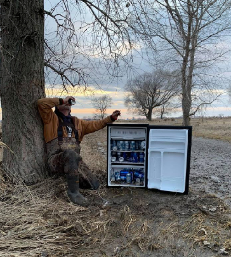 Image of man drinking beer from beer fridge outside