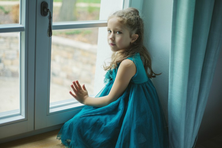 Image of sad girl looking out window.