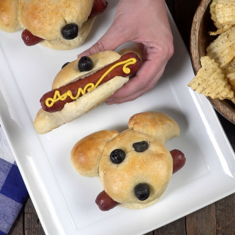 Putting mustard on hot doggie buns