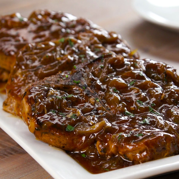 What's the easiest way to make pork chops so tender you won't need a knife? In the slow cooker, smothered with homemade caramelized onion & apple cider gravy.