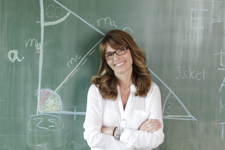 Smiling teacher standing at blackboard