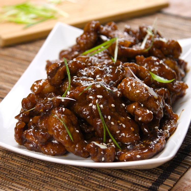 Pieces of Mongolian beef on white plate