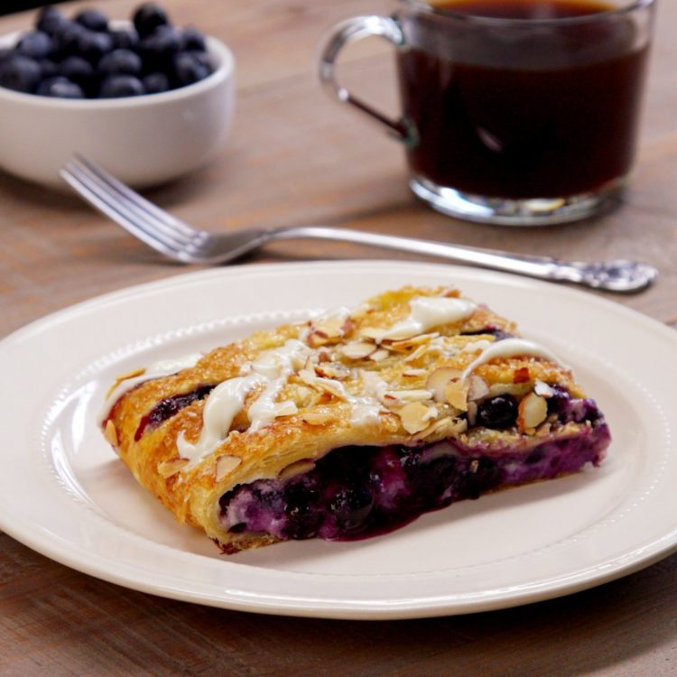Blueberry Breakfast Braid slice on plate almonds icing