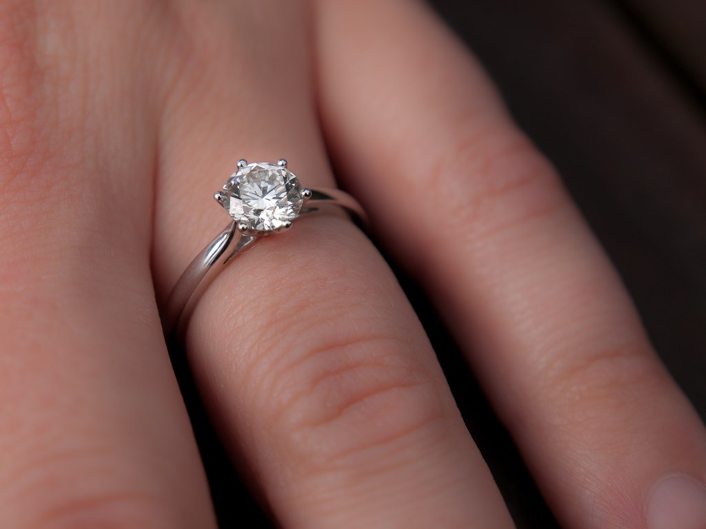 Woman wearing small engagement ring.