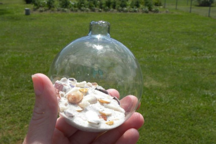 Small seashells and sand inside glass bulb ornament