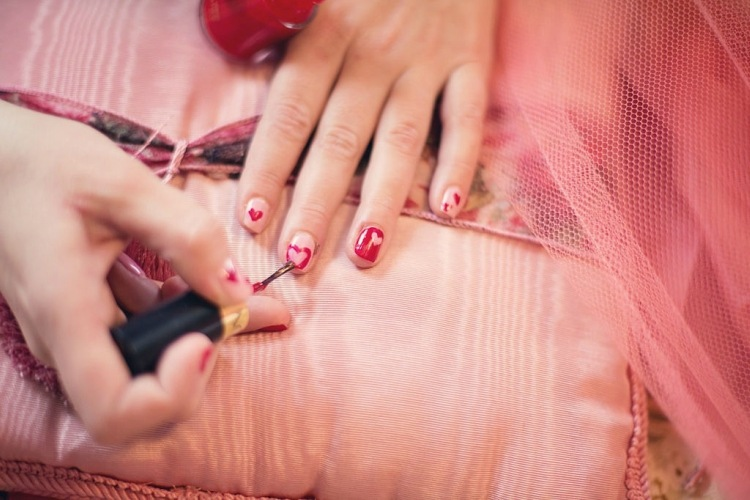 Painting nails with heart nail art on pink background