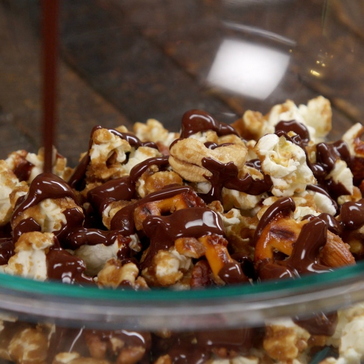 Add ¼ to ⅓ of the coated and cooled popcorn to thebowl of melted chocolate and gently mix to coat