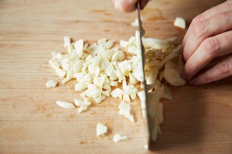 person mincing garlic