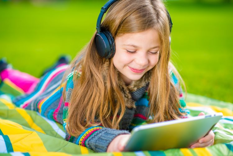 Image of girl on tablet with headphones