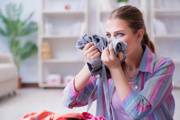 Image of woman sniffing clothes