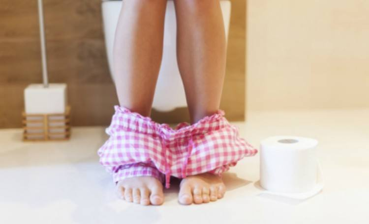 woman sitting on toilet with pajama pants down