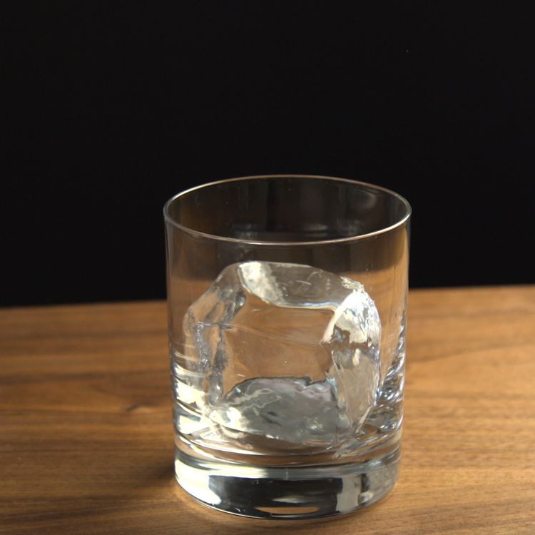Crystal Clear Cocktail Ice cube in empty glass black background