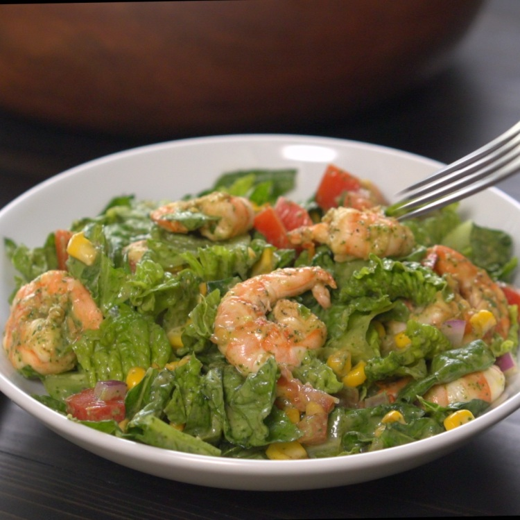 Fork descending on salad of shrimp, avocado and corn
