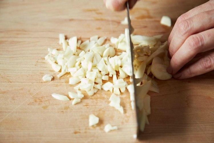 person mincing garlic