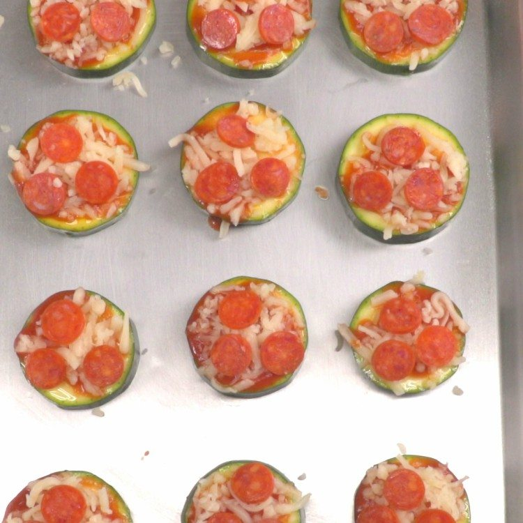 Overhead shot of zucchini pizzas on baking sheet