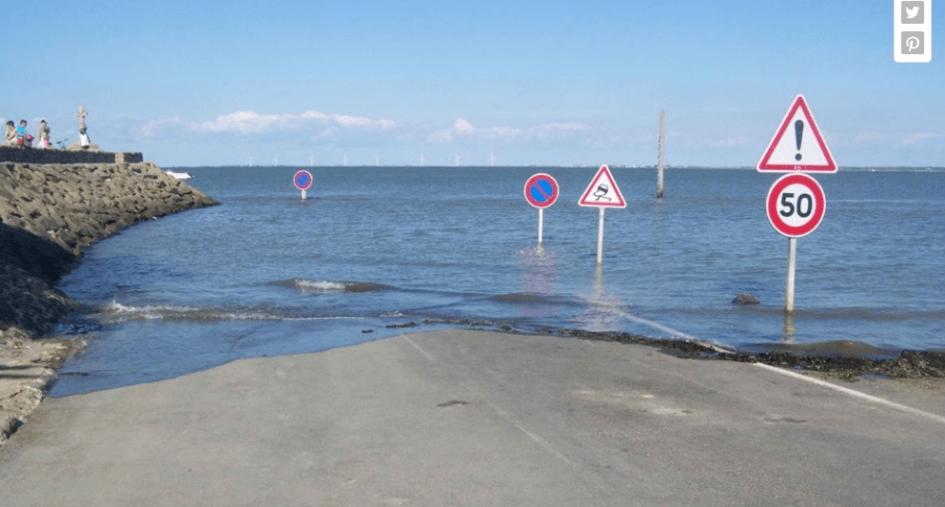 spectators watch as high tide submerges Passage du Gois