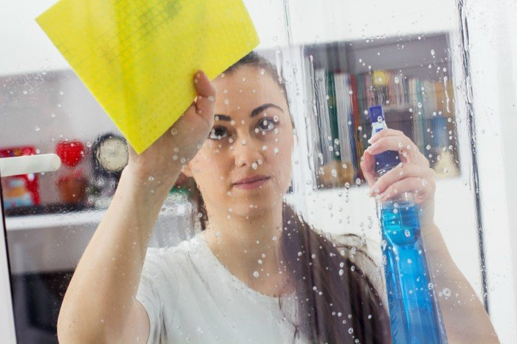Image of woman cleaning window.