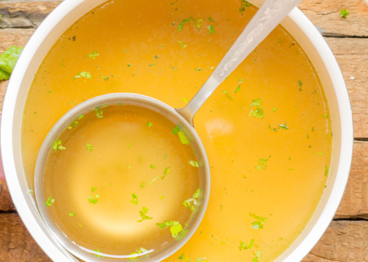 Image of Saucepan with broth on the table top view