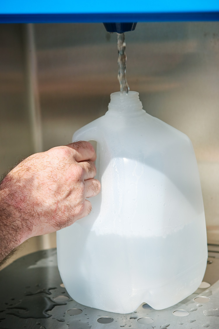 Closeup of a man's hand filling a gallon jug from a water machine.