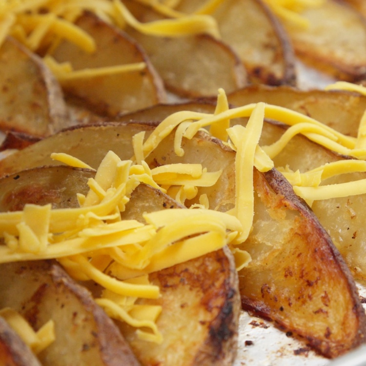 Sprinkle potato wedges with shredded cheddar cheese