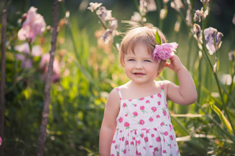 Image of baby girl with blue eyes blond hair and pink peony in her hair in summer garden with bright flowers. She dressed on white with floral pattern summer dress