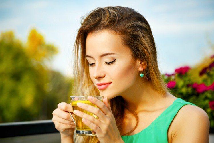 blonde woman drinks tea outside