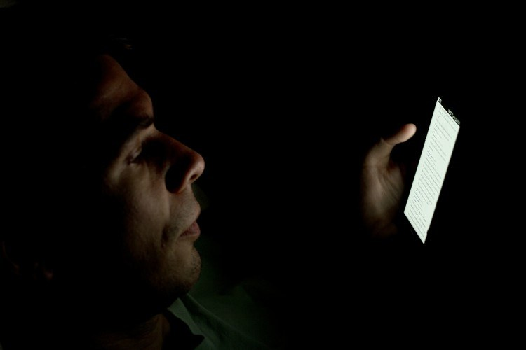 man looking at a cell phone in the dark