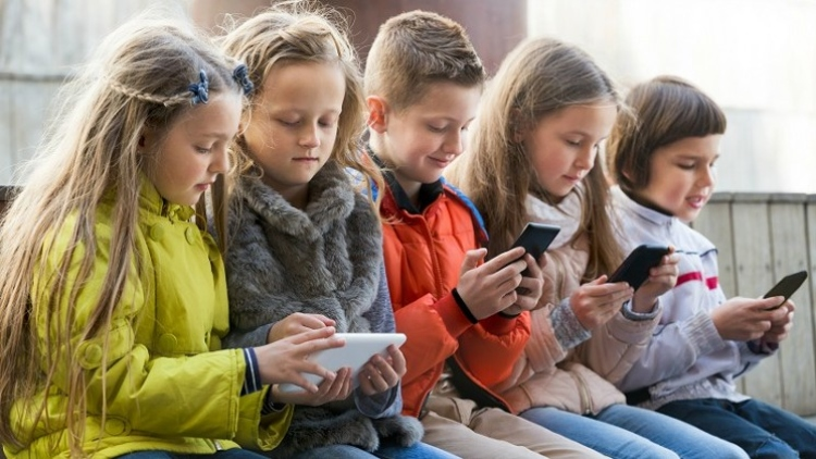 Image of children on mobile devices.
