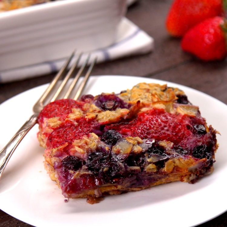 Serving of baked oatmeal with strawberries and blueberries on plate.